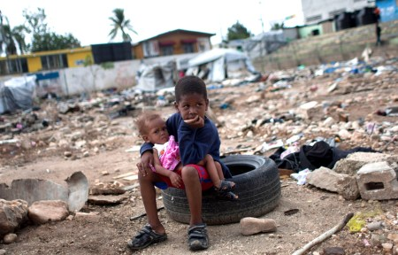 Six-year-old Charles Kerby hold his 11-month-old sister Mikerlina Dragon inside the Ste Therese camp, set up for people displaced by the 2010 earthquake, in Petion-Ville, Haiti, Saturday, June 16, 2012. Kerby had to drop out of school after the 2010 earthquake to help his working mother care for his two brothers and sisters. (AP Photo/Dieu Nalio Chery)