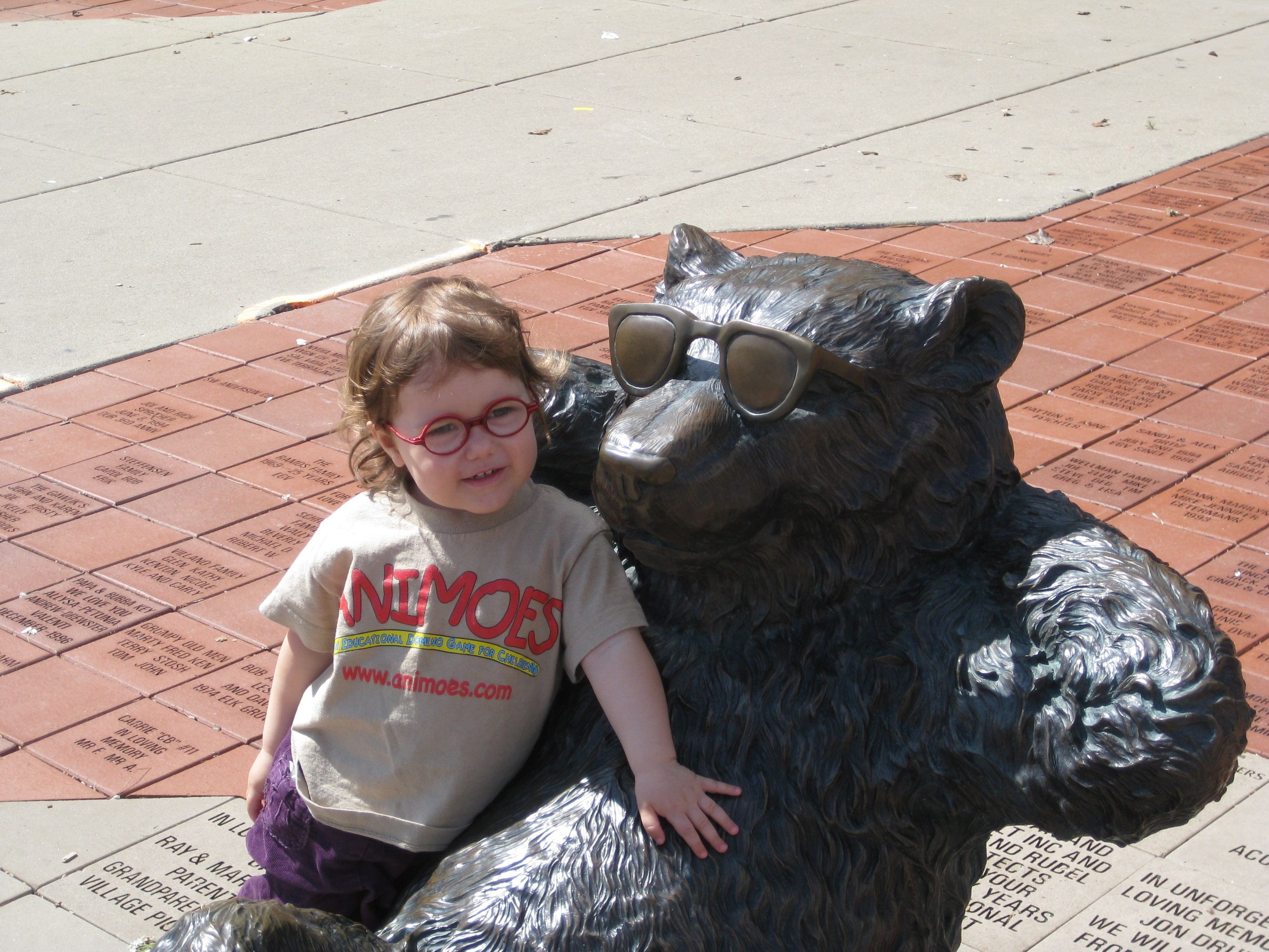 Glasses are uncommon on young children, and even less common in bear statues.