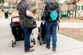 Parents with backpack and tote bag with toddlers stroller