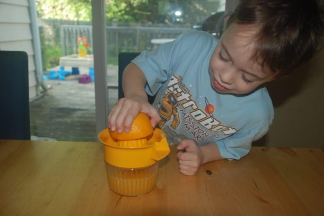 Cooking Up Some Fun with Kidstir - Toddling Around Chicagoland - Dexter squeezing an orange