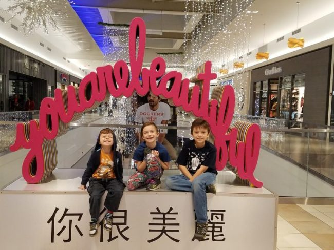 kids posed in front of You Are Beautiful art at Fashion Outlets of Chicago