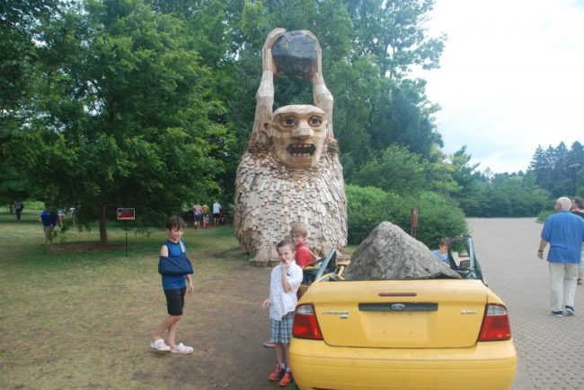 Giant troll with rock and crushed car