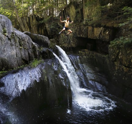 BOWDOIN COLLEGE GRANT EAST, ME - AUGUST 26: Dave Kallin leaps into a waterfall while hiking with his family at Gulf Hagas, a registered national landmark along the Appalachian Trail corridor. The Dresden family started out on the AT in Georgia in April and hopes to finish atop Mount Katahdin at the beginning of October. (Photo by Derek Davis/Staff Photographer)