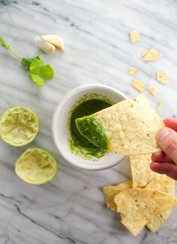 tortilla chip dipped into cilantro sauce