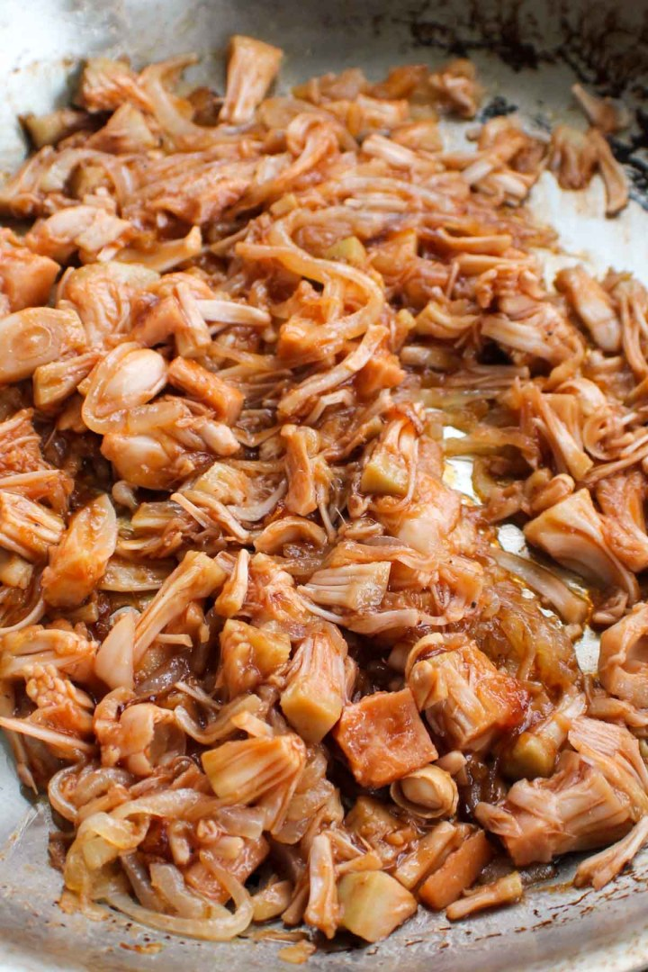bbq pulled jackfruit cooking in a pan with onions and garlic