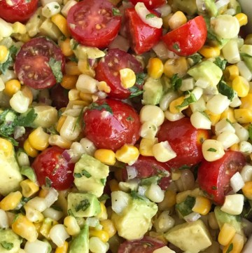 Avocado Corn Tomato Salad   Side Dish   Avocado   Healthy Recipe   Avocado Corn Tomato Salad is an easy, light, and refreshing salad! Chunks of avocado, sliced tomato and frozen corn are covered in an easy lime & olive oil dressing. Simple ingredients with amazing taste. Perfect for a light lunch, BBQ, potluck, or as a side for dinner. #healthy #salad #avocado #sidedish