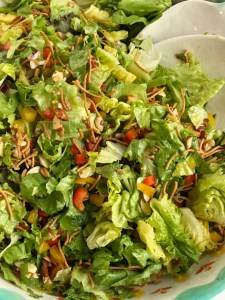 Company green salad is a perfect weeknight side dish or fancy enough for company! Crisp, bright greens with crunchy rice noodles, sweet red & yellow peppers, sugared almonds, salty sunflower kernels, and green onions. Topped with a simple dressing. This salad is surprisingly super easy and the perfect blend of texture, color, and flavor.