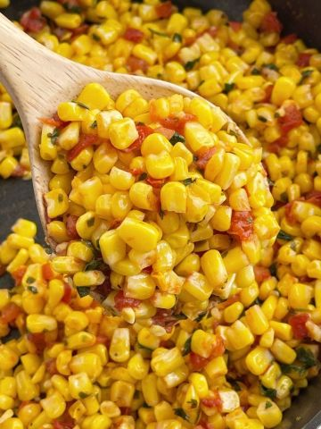 Southwestern corn recipe inside a skillet with a wooden spoon.