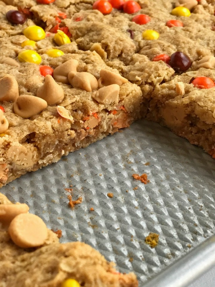 No flour triple peanut butter monster cookie bars are loaded with peanut butter, peanut butter chips, mini reese's pieces, and oatmeal! This recipe makes an entire cookie sheet of bars & they freeze perfectly. Perfect for lunchboxes or snacks for the week.