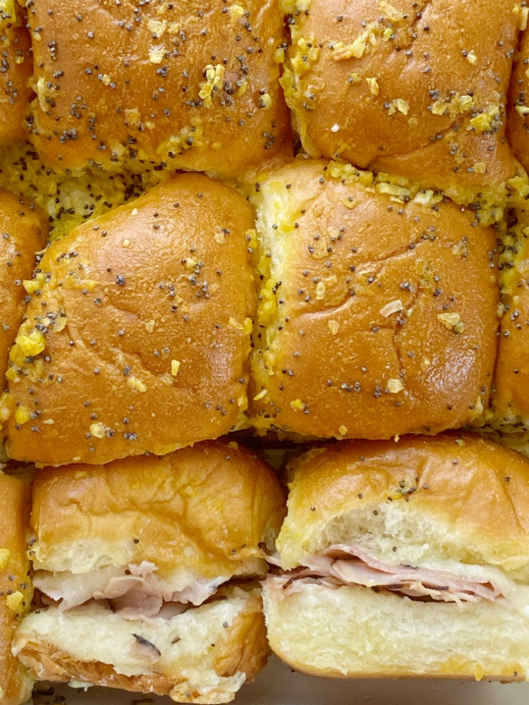 Baked Ham & Cheese Sandwiches are an easy family favorite dinner. Sweet Hawaiian rolls, deli sliced honey ham, shredded swiss cheese slathered in a delicious seasoned buttery sauce.