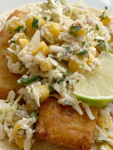 Easy Fish Tacos   Fish Taco Recipe   Easy Fish Tacos made with convenient frozen crispy fish sticks and a simple, 5 ingredient homemade cabbage slaw. Serve with corn tortillas for a simpler, and easier way to enjoy fish tacos. #fishtacos #easyrecipes #dinner #dinnerrecipes #tacos #tacorecipe