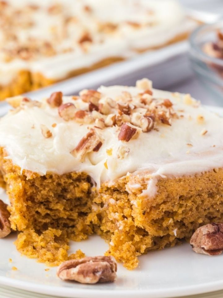 Close up shot of pumpkin spice sheet cake on a white plate and garnished with pecans.