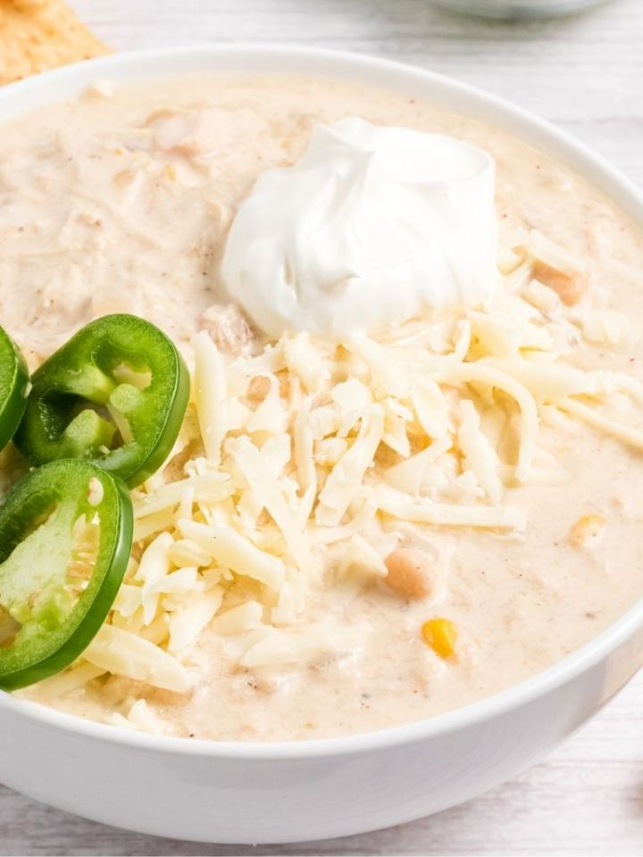 White chili garnished with jalapeño and sour cream.