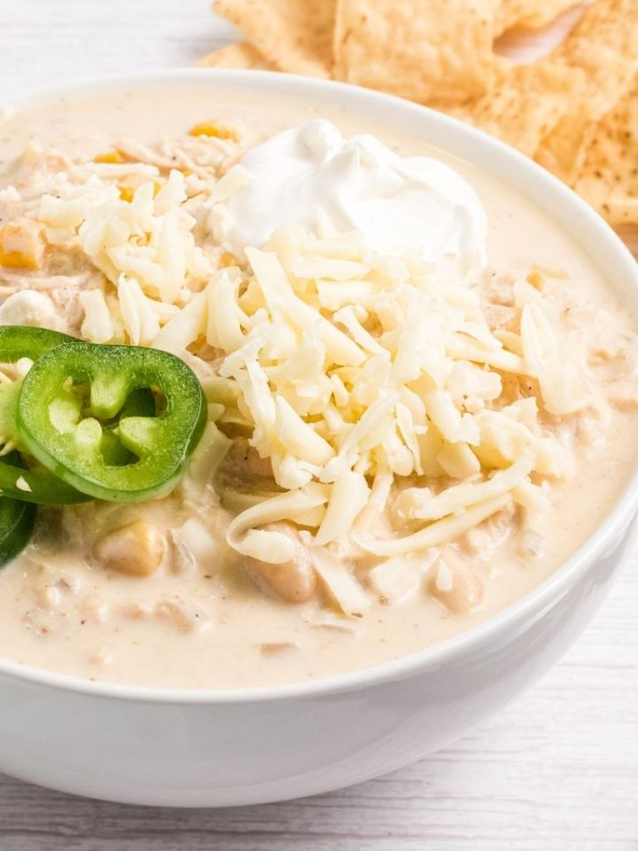 A white bowl with chicken chili inside of it topped with sour cream and jalapeño slices for garnish.