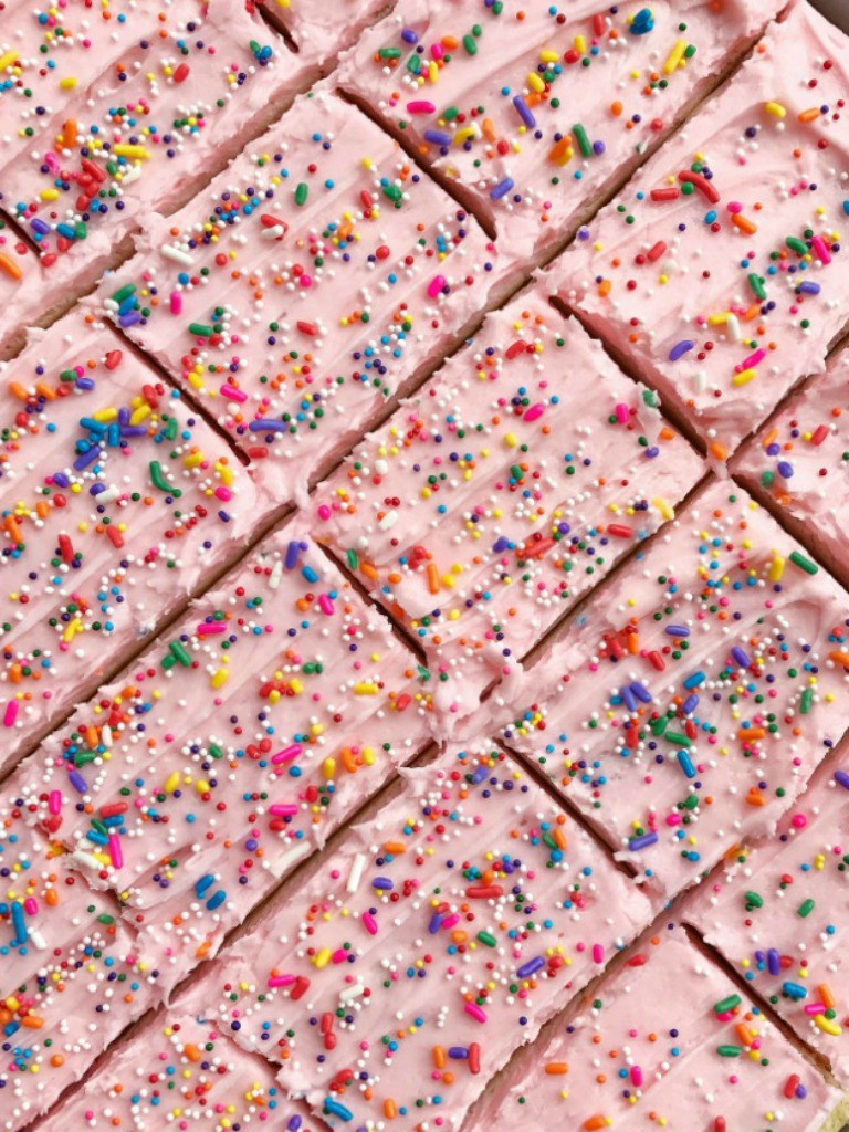 Soft, thick sugar cookie bars topped with a creamy and sweet frosting and baked in a sheet pan and perfect for a large crowd. Change up the frosting color & sprinkles for different events, parties, and/or birthdays