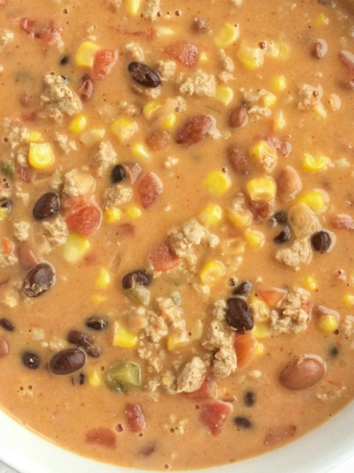 This easy cheesy taco soup take just minutes to prepare! Brown some ground turkey with spices and combine it with six cans. Melt some Velveeta cheese into it and you have a smooth, creamy, and super delicious quick dinner.