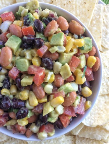 This hearty cowboy caviar chopped salsa is full of beans, veggies, lime, seasoning, and avocado! Perfect for game day, light lunch, BBQ, potluck, or as a healthier snack option. Chop up some vegetables and combine everything in a bowl.