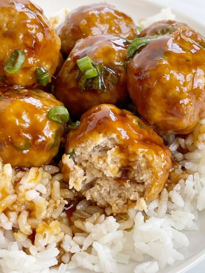 A plate with rice and chicken meatballs on it.
