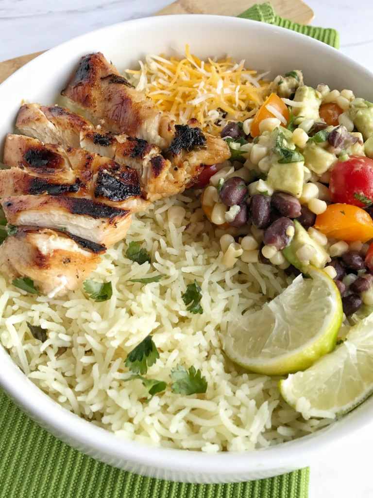 Skip the tortilla but still get all your favorite burrito fillings with these and honey cilantro lime grilled chicken rice bowls! Cilantro lime rice topped with fiesta avocado salsa, cheese, grilled honey lime chicken, and drizzled with creamy salsa verde sauce. These are so unbelievably good.