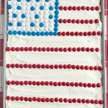 Sheet pan sugar cookie bars are perfect for Memorial Day gatherings or Fourth of July BBQ's! Soft, thick sugar cookie bars topped with a cream cheese frosting and decorated with red, white, & blue m&m candies for a festive and patriotic dessert.