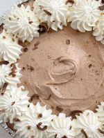 A double chocolate cream pie topped with whipped cream on a white background.