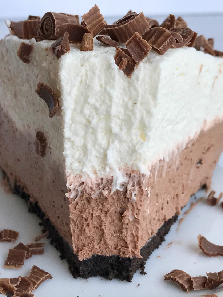 This easy, 5 ingredients double chocolate cream pie is a show stopper dessert with minimal effort. A chocolate crumb crust with two layers of chocolate cream; milk chocolate and white chocolate. Top with easy chocolate bar curls and you have a chocolate lovers dream pie!