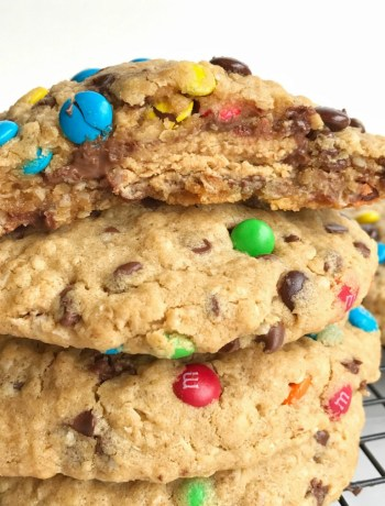 Giant Reese's stuffed monster cookies are the most delicious & indulgent dessert! Cookies bigger than your hand that are loaded with oats, peanut butter, chocolate chips, mini m&m's. The best part is the Reese's peanut butter cup stuffed inside.
