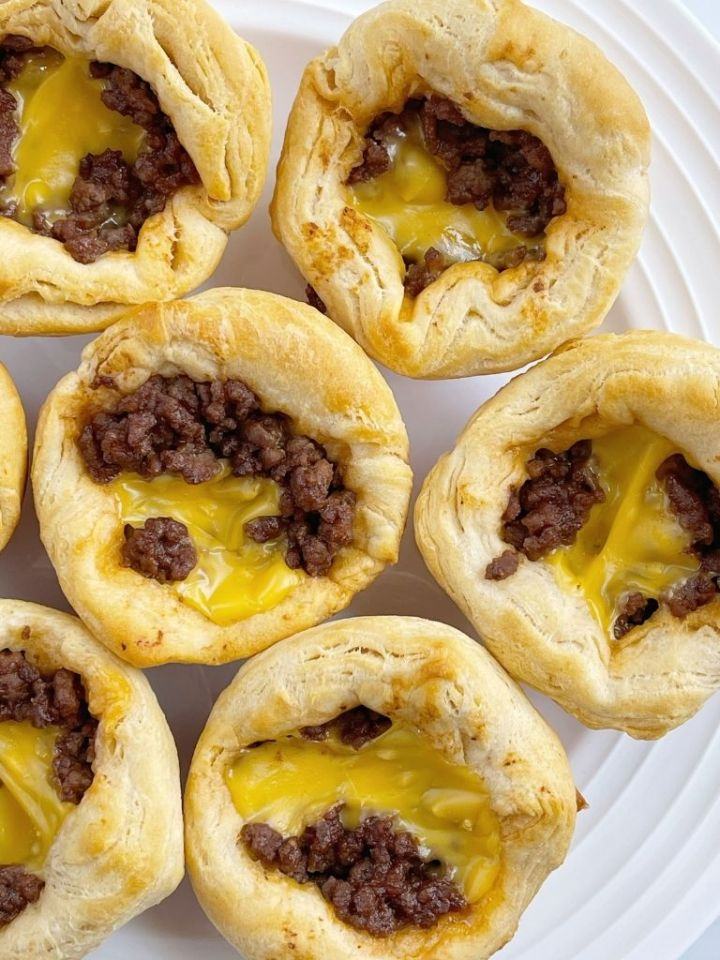 Picture of cheeseburger biscuit cups sitting on a white plate.