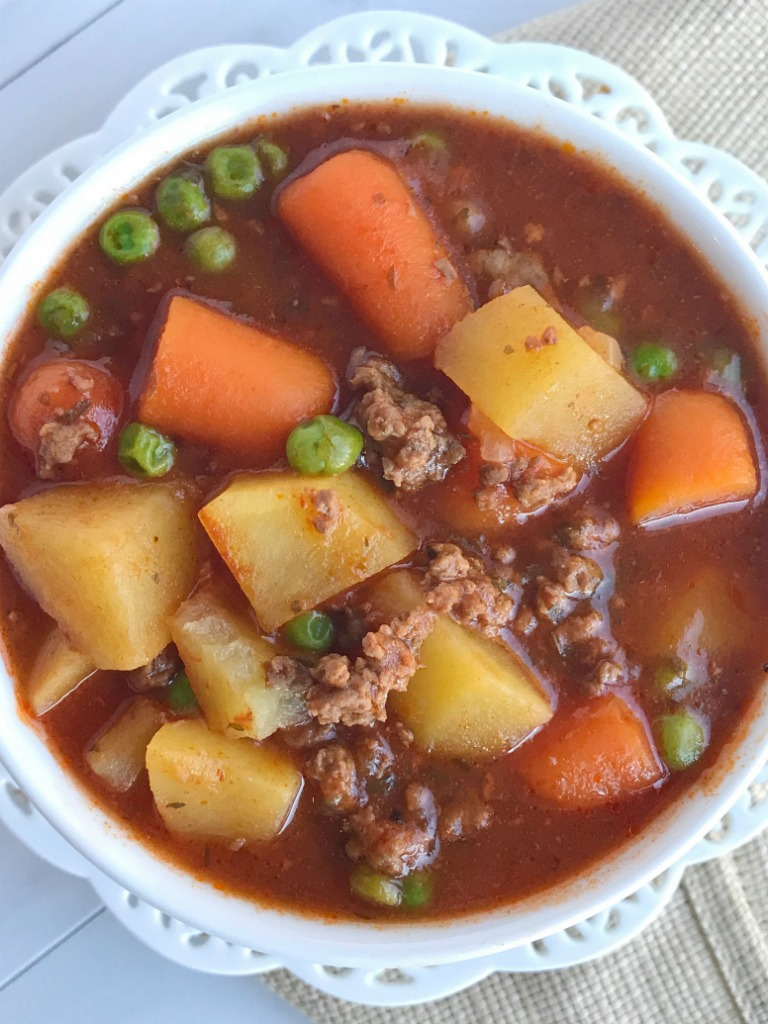 A few minutes prep in the morning is all you need for this hearty ground beef stew that is made in the slow cooker. A hearty , flavorful stew loaded with vegetables and ground beef. Perfect comfort food dinner recipe for any night of the week | www.togetherasfamily.com #stew #slowcookerrecipes #crockpotrecipes #groundbeef