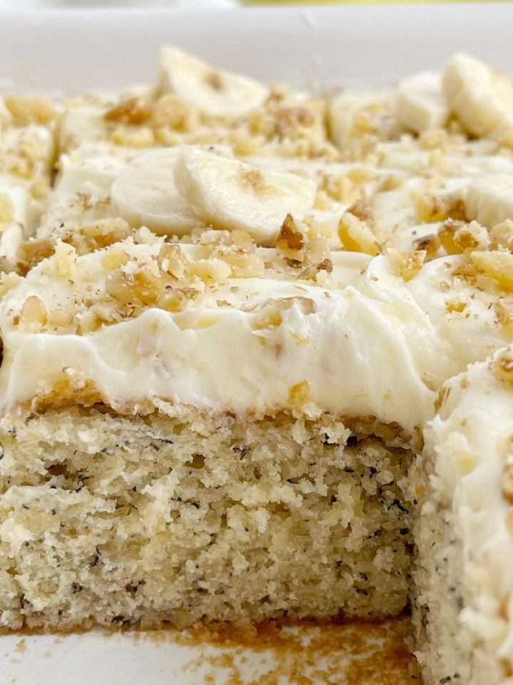 Banana Cake Recipe with cream cheese frosting, banana slices, and walnuts.