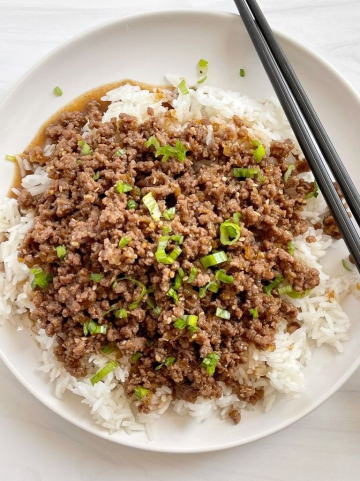 A white plate with ground beef teriyaki and chopsticks.