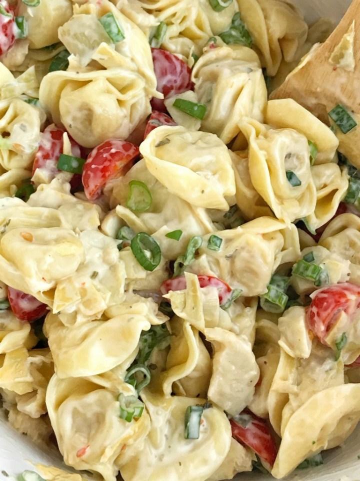 Creamy Tortellini Artichoke Pasta Salad   Creamy tortellini artichoke pasta salad requires only 5 ingredients! It's so quick & easy and perfect for a BBQ, picnic, light lunch, or a side dish. Marinated artichoke hearts, cherry tomatoes, green onions, tortellini, and creamy Italian dressing create a delicious pasta salad #pastasaladrecipes #artichokerecipes #tortellini