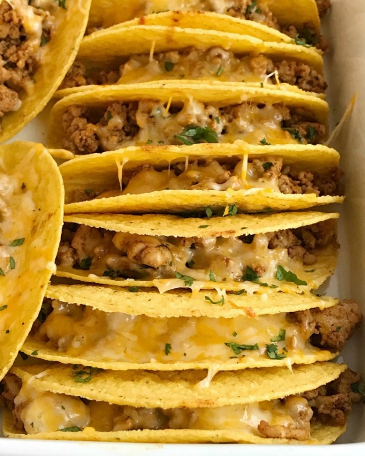 Baked Ground Chicken Tacos | Tacos | Mexican recipes | recipes with ground chicken | Baked ground chicken tacos are an easy, 30 minute dinner recipe! Crispy corn taco shells are filled with tender and flavorful ground chicken with homemade taco seasoning. So much flavor and healthy too! Load up the cheesy crispy tacos with all your favorite toppings #tacos #easydinnerrecipes #dinner #groundchicken #mexicanfood