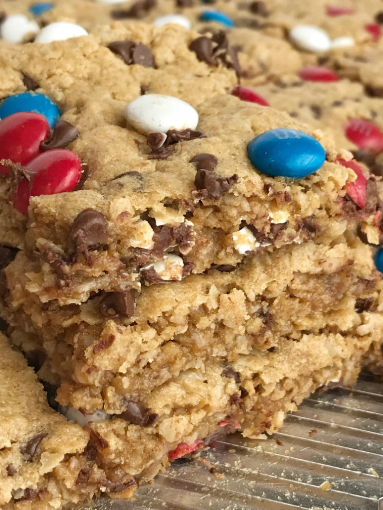 No Flour Red, White, & Blue Cookie Bars   No Flour Desserts   Gluten Free   Cookie Bars   Monster Cookies   Celebrate Memorial Day and 4of of July with these fun and festive no flour red, white, & blue cookie bars. Cookie bars with no flour and loaded with peanut butter, oats, chocolate chips, and m&m's. This holiday dessert recipe will be the hit of the BBQ. Makes an entire cookie sheet so there is plenty to serve a crowd. #glutenfree #4thofjuly #patriotic #easydessertrecipes