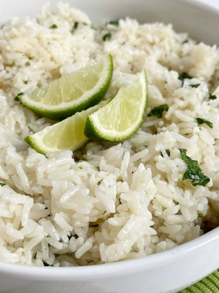 A close up picture of cilantro lime rice inside a white bowl.