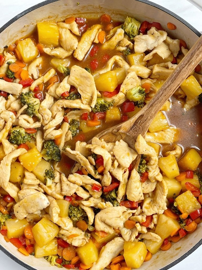 A white pan with teriyaki chicken pineapple stir fry in it and a wooden spoon.