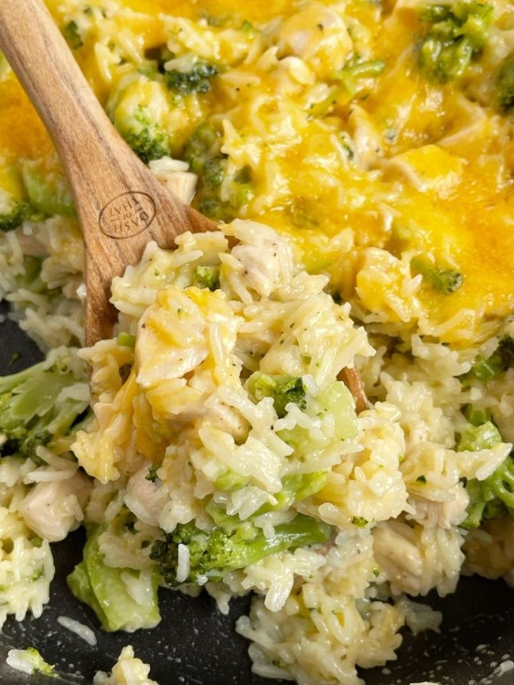 One scoop of chicken broccoli rice on a wooden spoon.