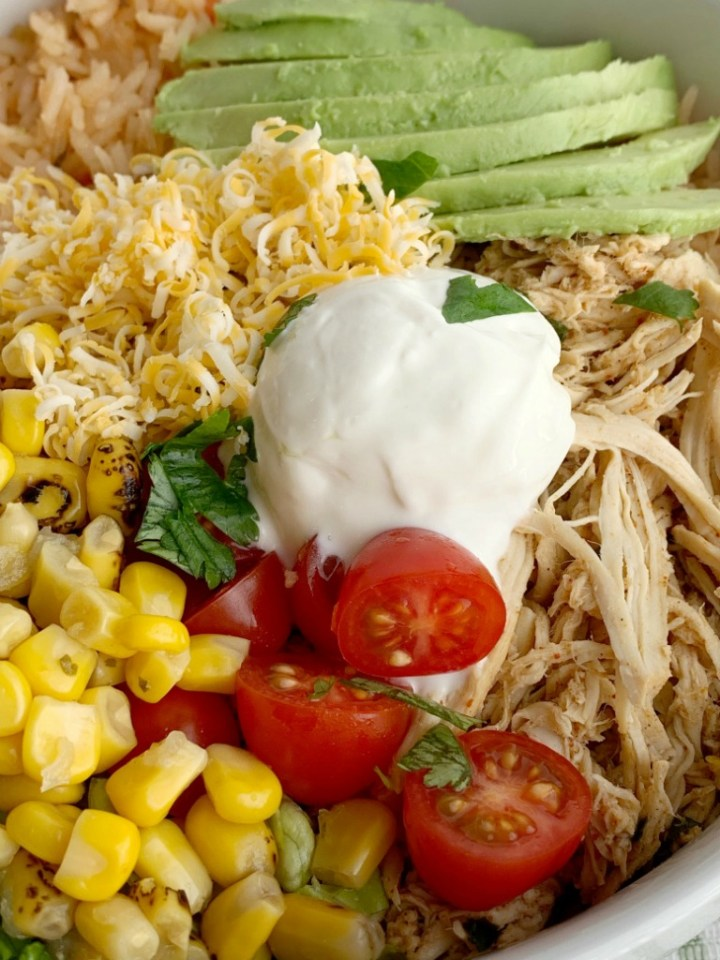Lime Chicken Taco Bowls | Taco Bowls | Crockpot Recipe | Taco Bowls loaded with perfectly shredded and seasoned lime chicken that's made in the crock pot! Serve with rice, corn, lettuce, cheese, avocado, and salsa for a delicious, make it yourself dinner. #mexicanfoodrecipes #mexicanfood #dinnerideas #tacobowls #crockpotrecipes #slowcooker