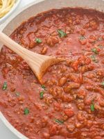 Picture of meat sauce inside a pan with a wooden spoon. Serve meat sauce over spaghetti noodles.
