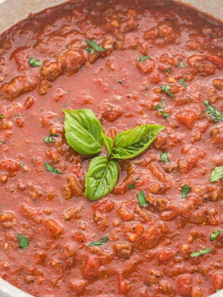 A pan of spaghetti meat sauce with a basil leaf in the center.