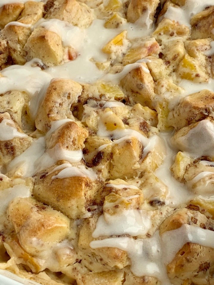 Peaches n' Cream Cinnamon Roll Casserole | Cinnamon Roll Casserole | Breakfast Recipes | Cinnamon Roll Casserole with peaches n' cream. Frozen peaches, cream cheese, powdered sugar, and cinnamon rolls combine to create the best sweet breakfast treat. Only 4 ingredients needed! #breakfastrecipes #casserole #cinnamonrolls #peaches #breakfastcasserole #recipeoftheday
