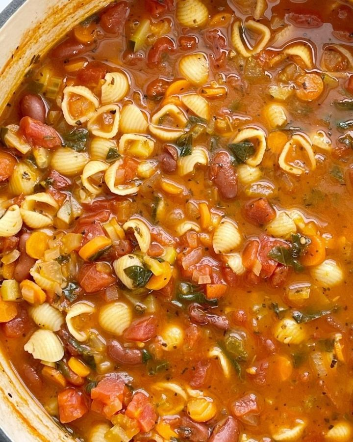 Pot of minestrone soup with pasta, beans, vegetables in a tomato sauce vegetable broth base.