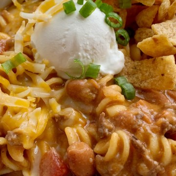 Ground Beef Chili is a fun variation to classic chili! Loaded with beef, seasonings, tomatoes, pinto beans, and tender pasta. Best part is the homemade queso sauce in the ground beef chili!