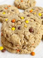 A stack of peanut butter monster cookies on a white cookie sheet.