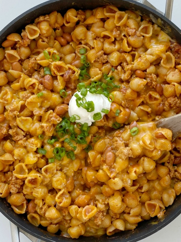 Turkey Chili Mac and Cheese is made in just one pot! Ground turkey chili with pinto beans cooks in a seasoned tomato sauce and chicken broth base with small shell pasta. Add lots of cheese for a cheesy and creamy mac and cheese with turkey chili!