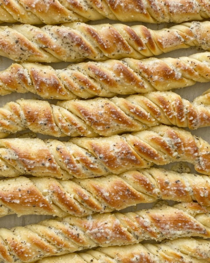 Easy Breadsticks Recipe are a family favorite because of their fun twisty shape. Quick & easy to make and the perfect recipe for beginners. Soft breadsticks filled with garlic butter and topped with parmesan seasoned butter.