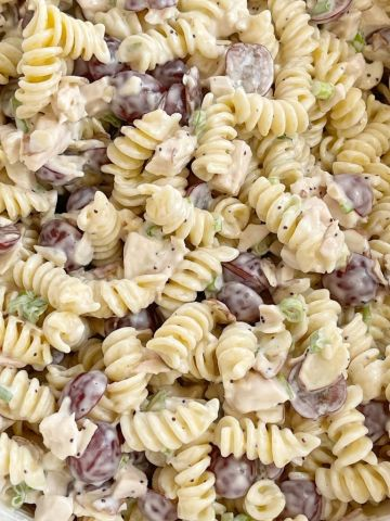 A close up picture of poppy seed chicken pasta salad with grapes in it.