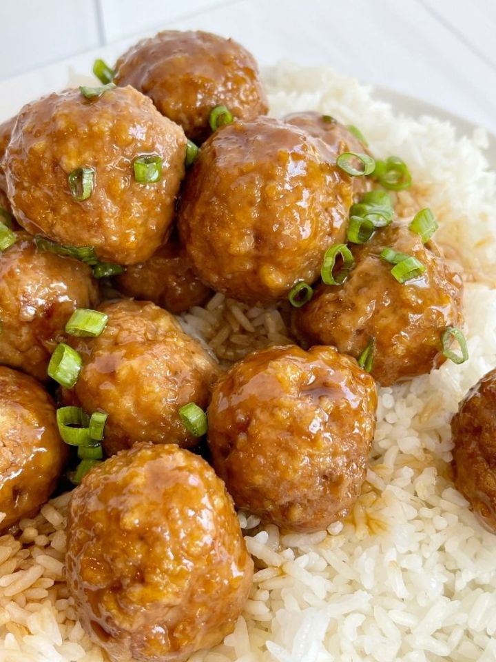 Turkey meatballs on top of rice on a white plate.