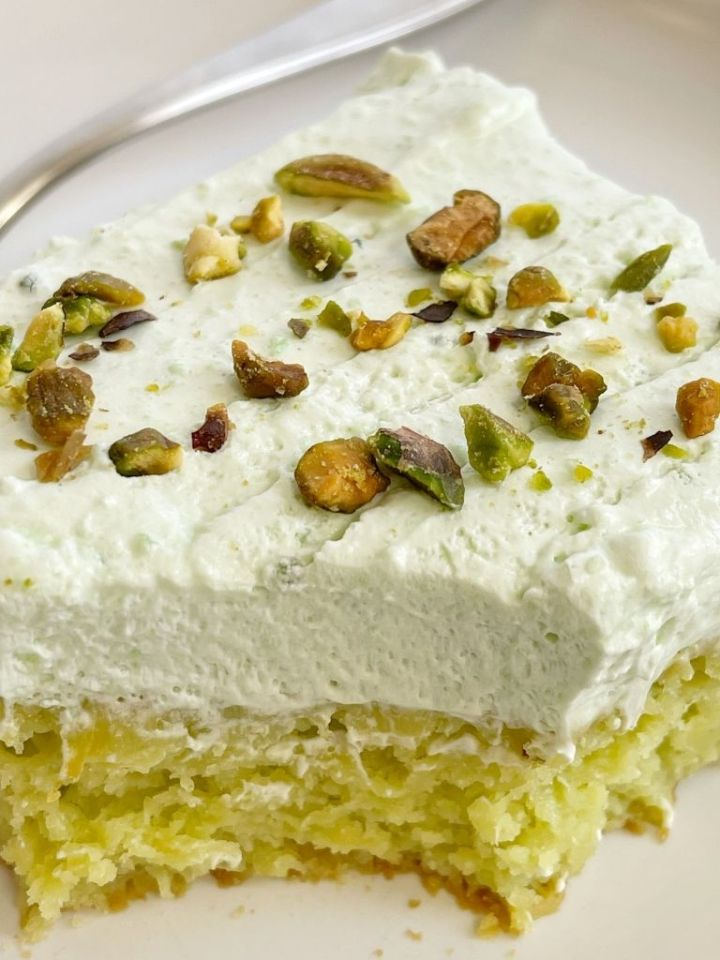 Slice of pistachio cake with frosting and pistachios on top of the cake slice.