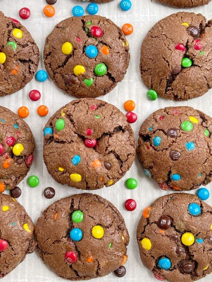 An overhead shot of a tray of chocolate mm cookies with mm candy on the sides of the pan.